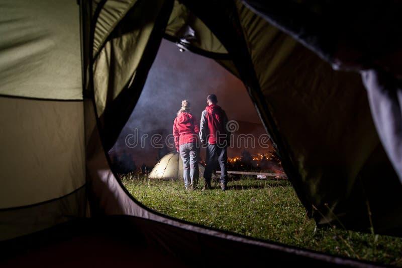 Vista do interior da barraca em caminhantes dos pares no acampamento da noite fotos de stock royalty free