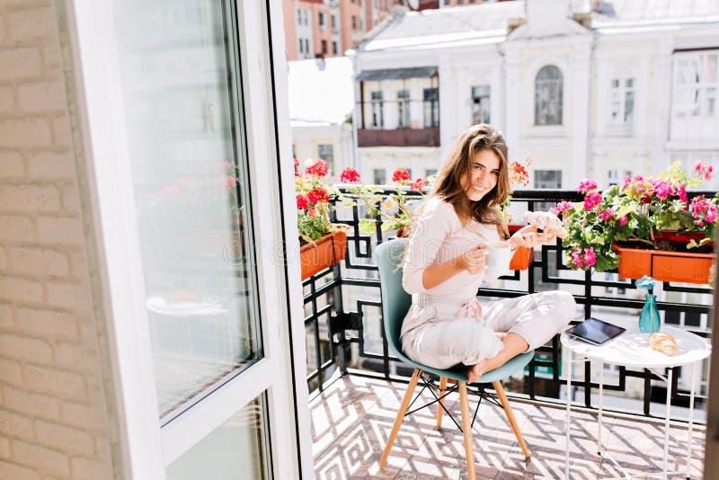 Vista do interior da moça bonita que come o café da manhã em flores da bordadura do balcão na manhã na cidade Guarda um copo imagem de stock
