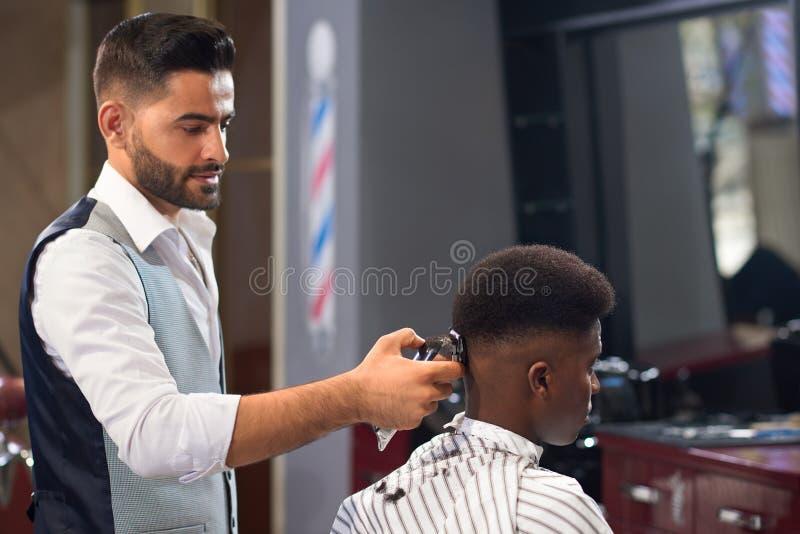 Vista do lado do barbeiro que faz o corte de cabelo na moda na barbearia fotografia de stock