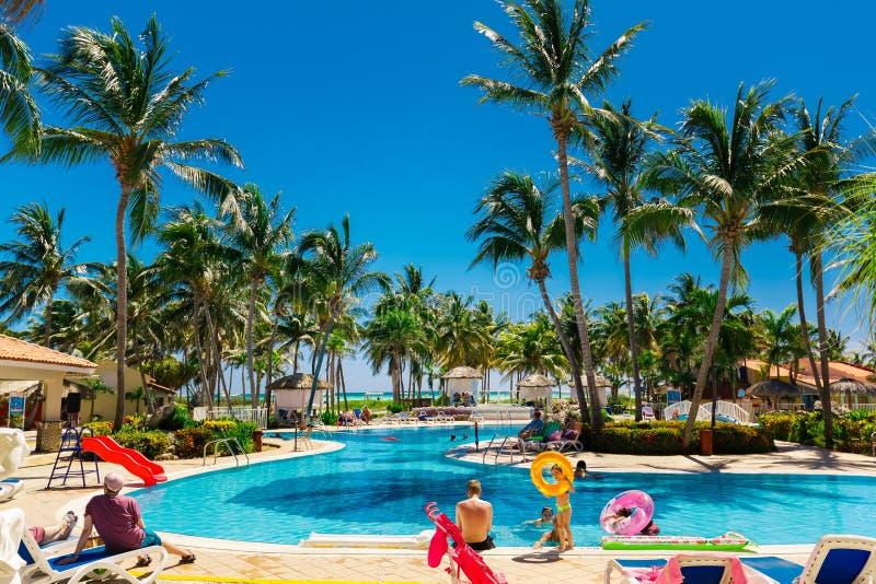 Vista do lado da entrada do hotel em convidar a piscina tropical do jardim com os povos e as crianças que apreciam seu tempo foto de stock