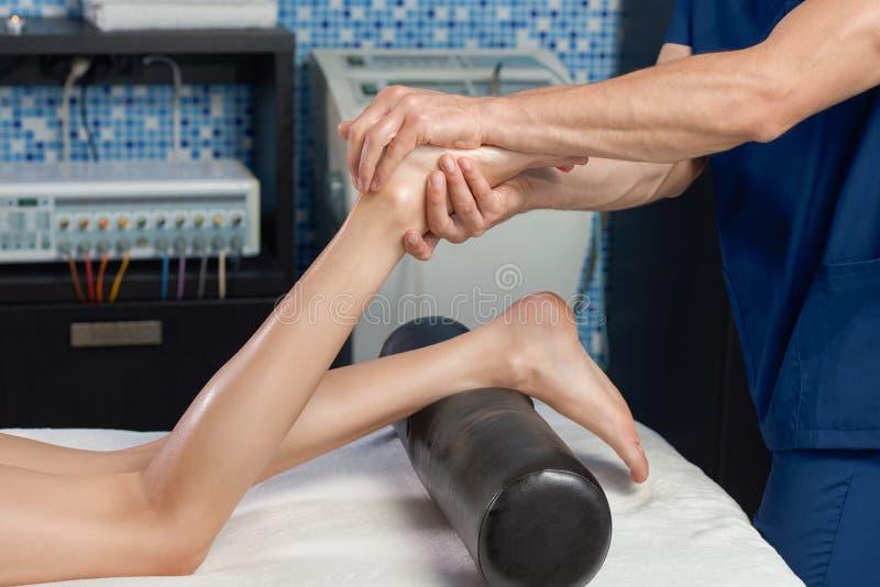 Vista do lado de fazer massagens os pés do cliente fêmea nos termas fotos de stock