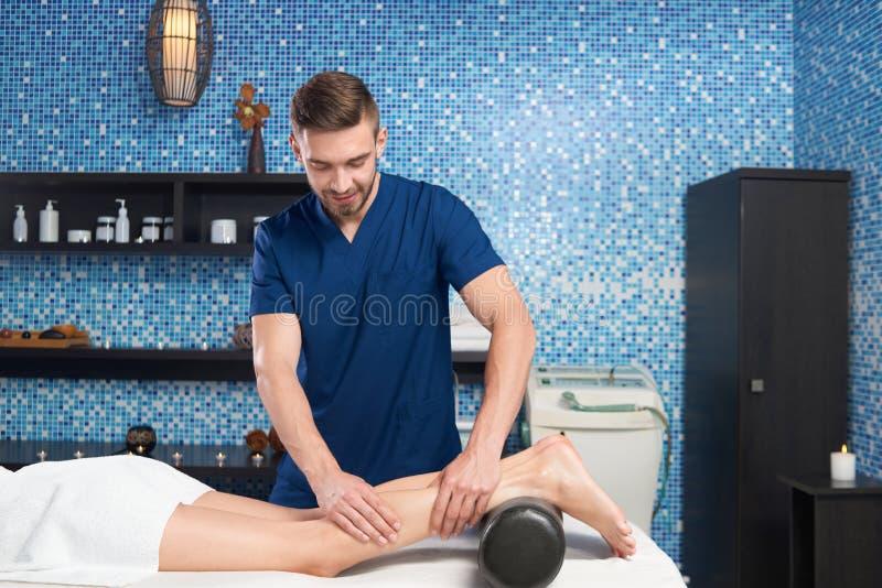 Vista do lado do doutor que faz massagens os músculos da vitela do cliente fotografia de stock royalty free
