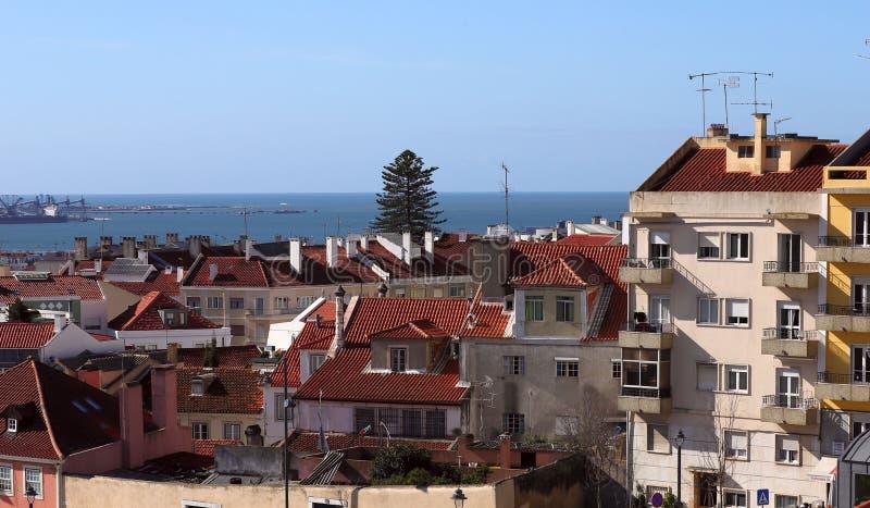 Vista do lado nos telhados das casas sob as telhas vermelhas contra o céu azul com nuvens brancas e o horizonte do oceano foto de stock