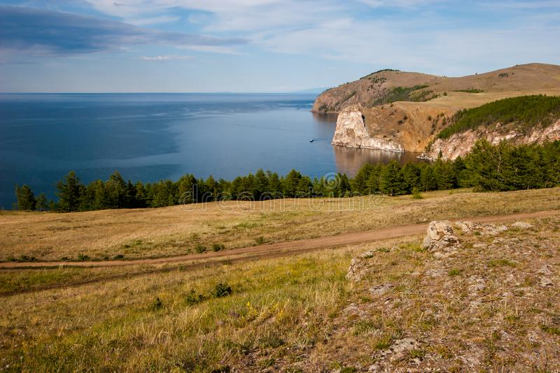 Vista do Lago Baikal com um penhasco e um navio No primeiro plano é uma estrada secundária imagens de stock royalty free
