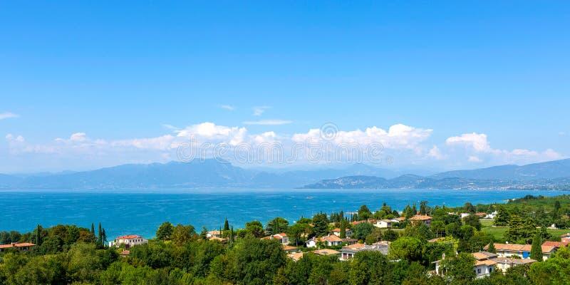Vista do lago Garda, paisagem do verão Lago azul, cumes dos mountayns Castelnuovo del Garda, Itália foto de stock