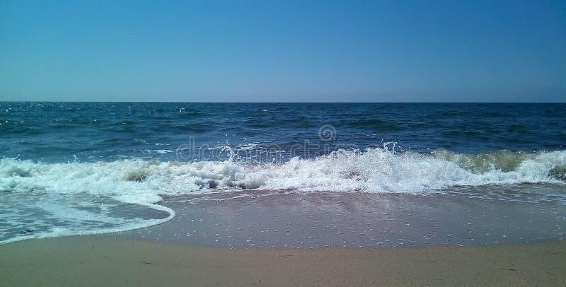 Vista do mar da costa em um dia ensolarado Mar calmo com ondinhas claras na superfície da água e das ondas pequenas fotos de stock royalty free