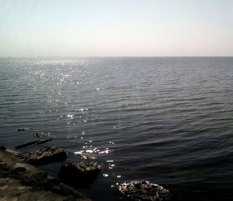 Vista do mar da costa em um dia ensolarado Mar calmo com ondinhas claras na superfície da água e das ondas pequenas imagem de stock