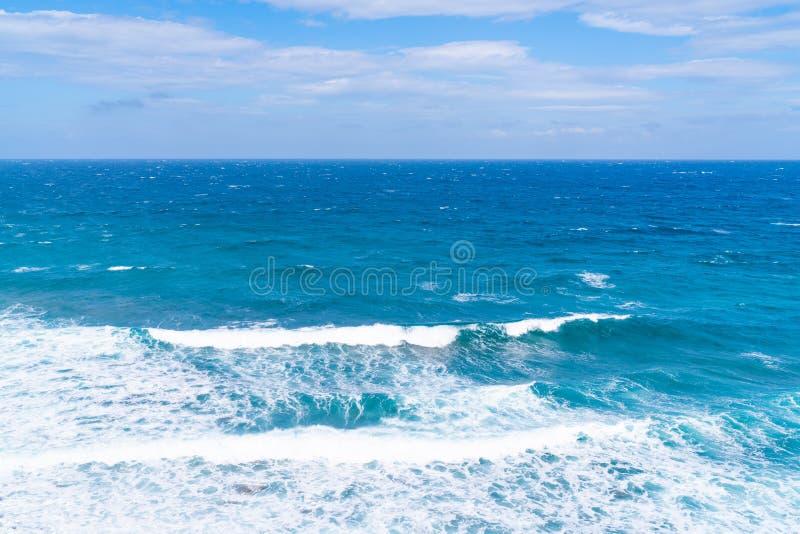Vista do Mar Egeu com as ondas que esmagam o aginst a costa, paisagem de Santorini foto de stock