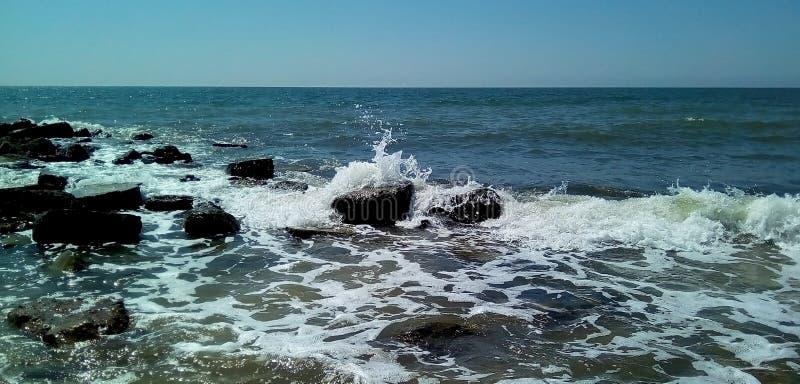 Vista do mar em um dia ensolarado No primeiro plano são as ondas pequenas com espirram e a espuma branca, pedras escuras molhadas fotografia de stock royalty free