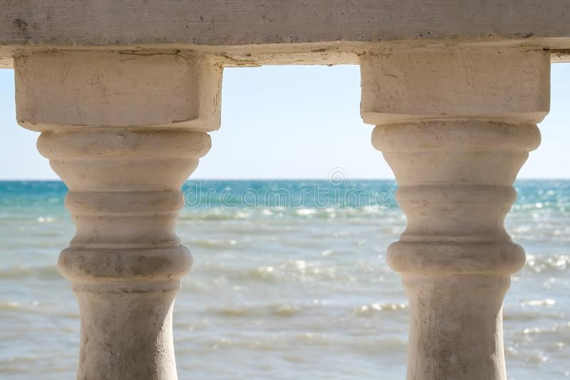 Vista do mar rippling através das colunas velhas da cerca fotos de stock