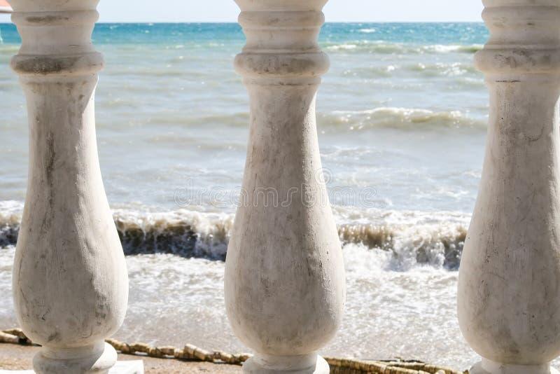 Vista do mar rippling através de três colunas velhas da cerca fotografia de stock royalty free