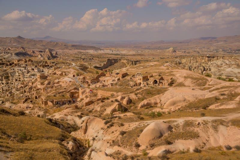 Vista do monte às casas turcas tradicionais nas rochas na vila Cavusin perto de Goreme em Cappadocia Turquia fotos de stock