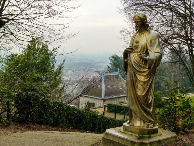 Vista do nebuloso, inverno Lyon de um trajeto da montanha com uma estátua de bronze no primeiro plano, França imagens de stock
