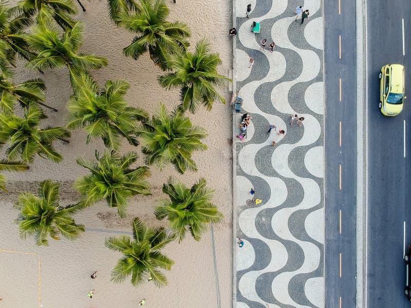vista do passeio à beira mar de Copacabana durante o fim da tarde, tomada com um zangão, com a textura de pedra portuguesa famosa imagem de stock