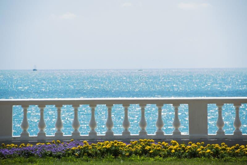 Vista do passeio ensolarado com as flores na costa bonita da costa de mar na cidade Pavimento de pedra perto da praia e foto de stock