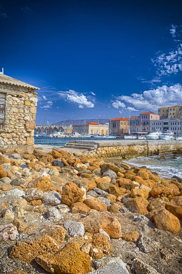 Vista do porto e de barcos Venetian velhos de Chania no fundo Lotes das pedras em Sandy Beach na parte dianteira fotos de stock royalty free