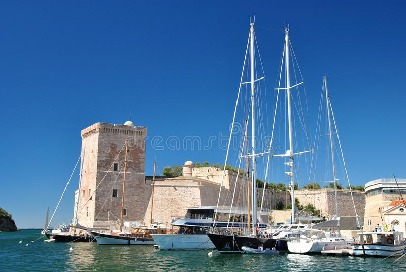 Vista do porto velho de Marseill: torre de pedra quadrada do forte Saint-Jean e de barcos de navigação bonitos imagens de stock