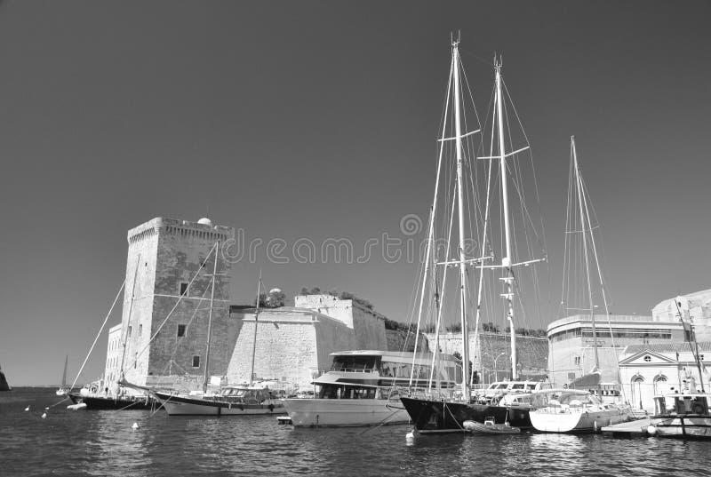 Vista do porto velho de Marseill: torre de pedra quadrada do forte Saint-Jean e de barcos de navigação bonitos imagens de stock royalty free