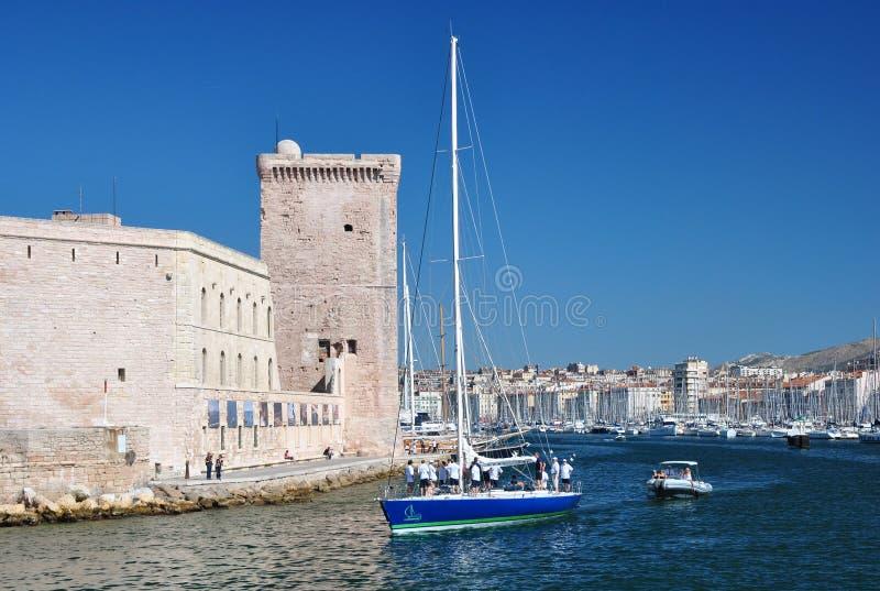 Vista do porto velho de Marselha com muitos iate e barcos de navigação e de uma torre de pedra quadrada do forte Saint-Jean fotografia de stock