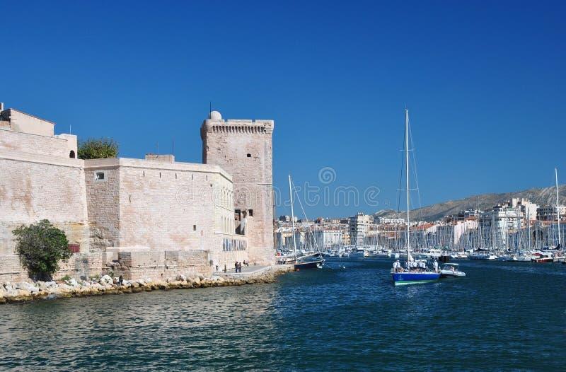 Vista do porto velho de Marselha com muitos iate e barcos de navigação e de uma torre de pedra quadrada do forte Saint-Jean fotos de stock