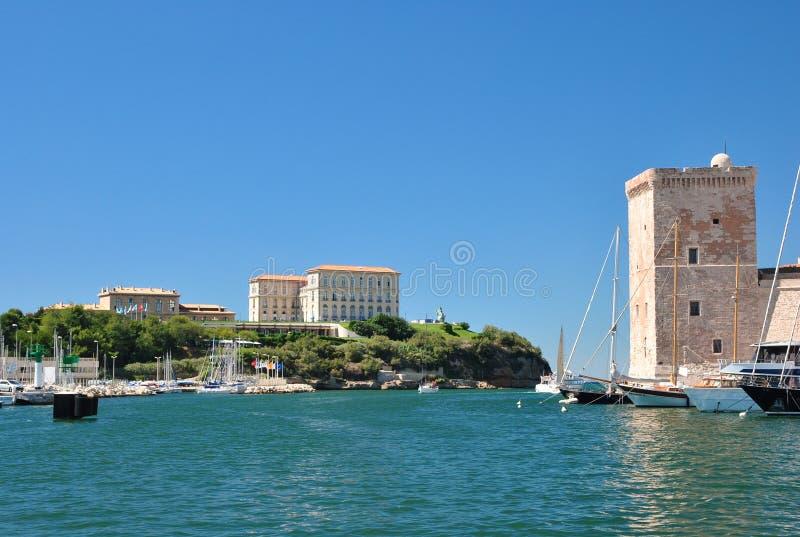 Vista do porto velho de Marselha com prédios de apartamentos modernos e de uma torre de pedra quadrada do forte Saint-Jean fotografia de stock