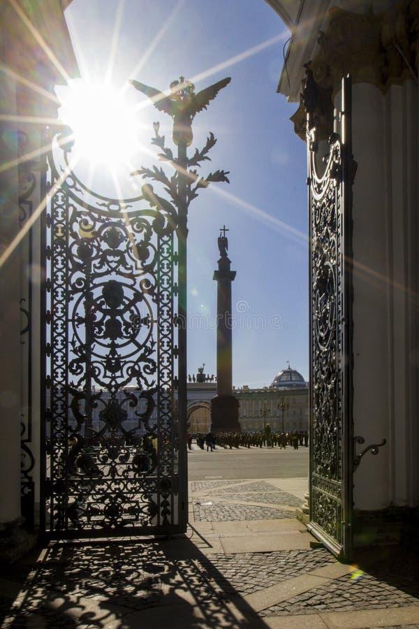 Vista do quadrado do palácio, do arco do estado maior geral e da coluna Alexandrian com anjo com um aberto - porta do ferro fundi fotografia de stock royalty free