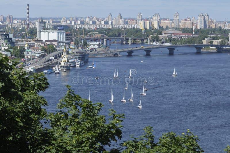 Vista do rio, das construções e dos veleiros de Dnieper flutuando na água fotografia de stock