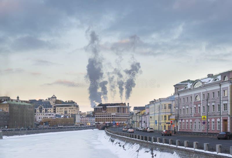 Vista do rio no por do sol, rio congelado de Moscou, construções ao longo da margem, tubulações de vapor, o céu com nuvens, inver fotografia de stock
