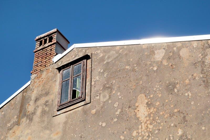Vista do telhado da construção velha, janela quebrada dentro, portal do telhado, close up fotografia de stock