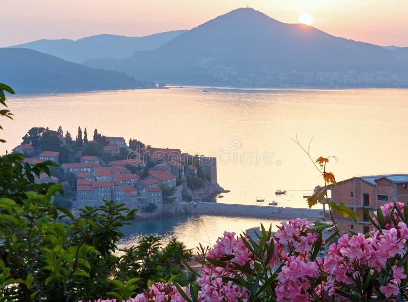 Por do sol sobre a ilhota do mar de Sveti Stefan (Montenegro) foto de stock