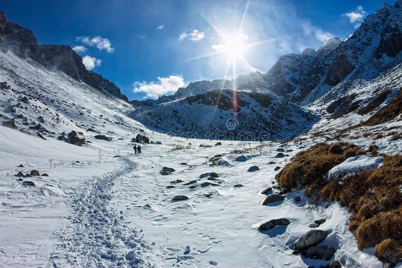 Vista do vale à parte superior das montanhas nevados sob o céu azul fotos de stock