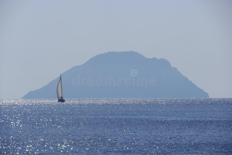 Vista do veleiro com uma ilha no fundo, ilhas eólias, Sicília fotos de stock royalty free