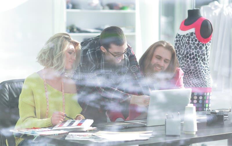Vista do vidro de trás grupo de desenhistas que trabalham em esboços novos fotos de stock