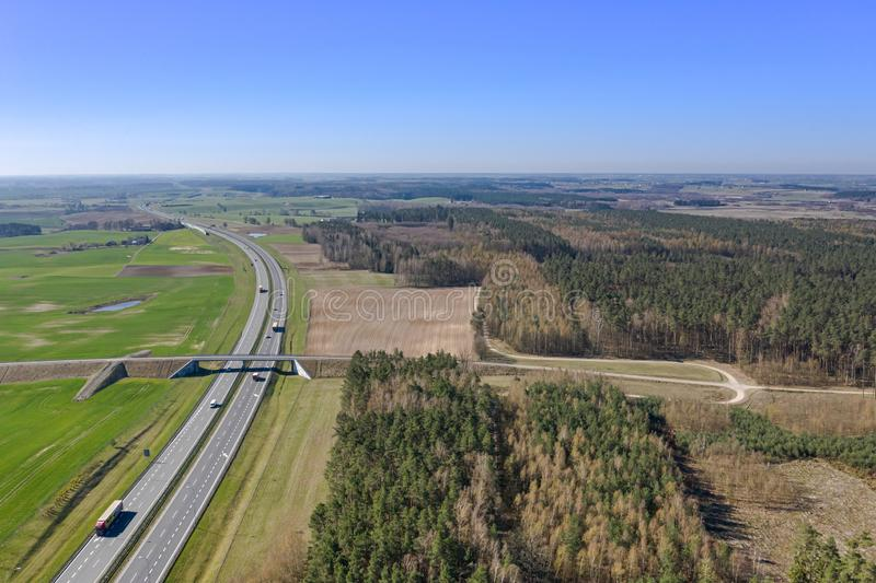 Vista do zangão na estrada com carros moventes, esticando afastado entre os campos e as florestas fotos de stock royalty free
