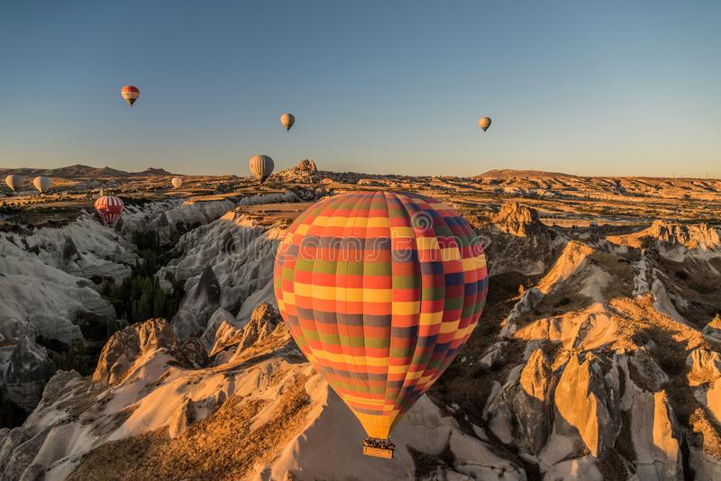 Vista dos balões de ar quente que voam por todo o lado na região de Cappadocia durante o nascer do sol, Turquia foto de stock royalty free