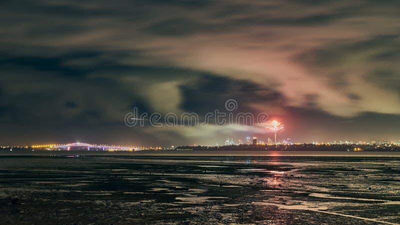 Vista dos fogos de artifício através da baía da península de Te Atatu para a cidade de Auckland foto de stock royalty free