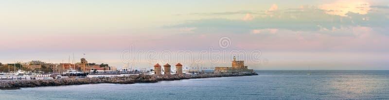 Vista dos moinhos de vento e do farol no porto de Mandraki, o Rodes, Grécia imagem de stock