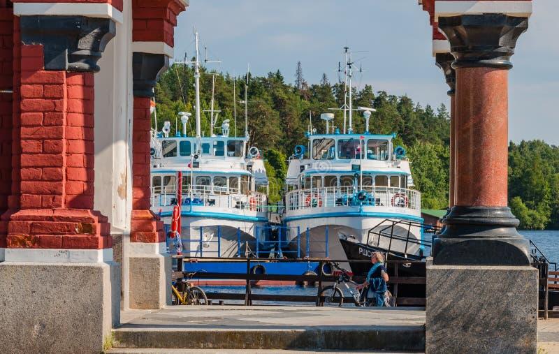 Vista dos navios no cais do monastério de Valaam através das colunas da capela do ícone da mãe do deus de tudo fotografia de stock