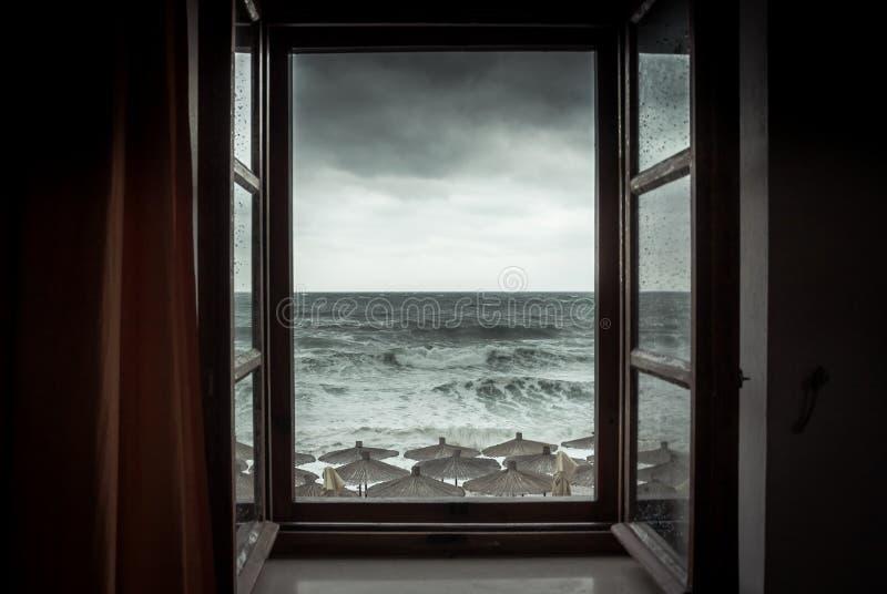 Vista drammatica del mare dalla finestra aperta con le grandi onde tempestose e dal cielo drammatico durante pioggia ed il tempo  fotografia stock
