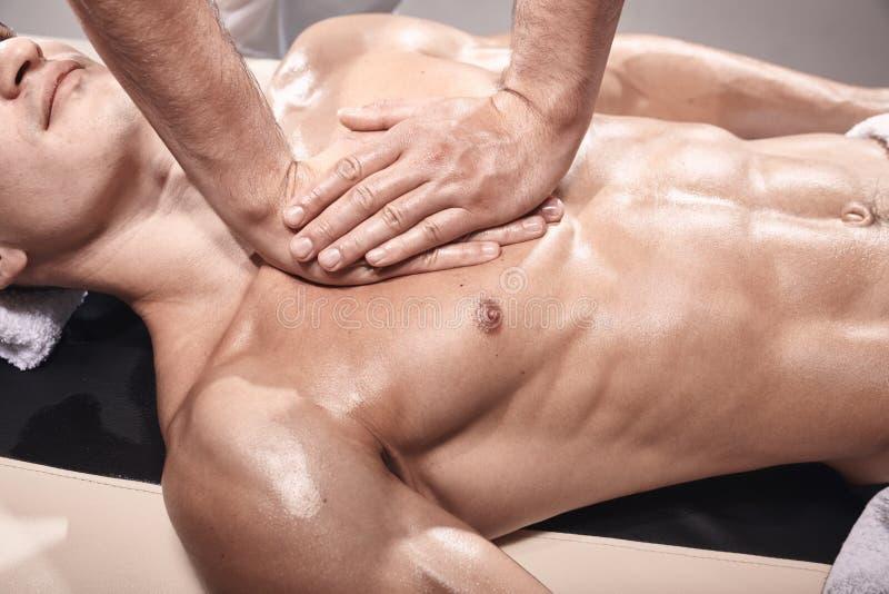 Vista elevada, dois homens novos, 20-29 anos velhos, fisioterapia dos esportes dentro no est?dio, sess?o fotogr?fica O massagista imagem de stock