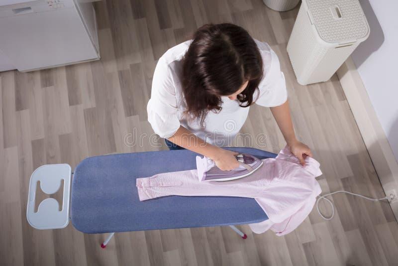 Vista elevado de um pano passando da mulher na lavandaria foto de stock royalty free
