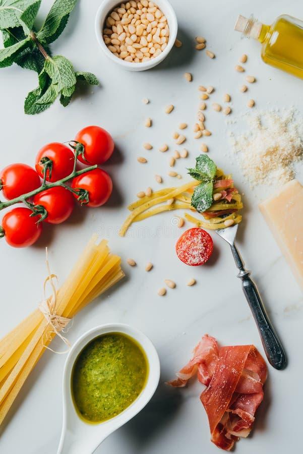 vista elevata della forcella avvolta da pasta circondata dai pinoli, pesto, parmigiano, spaghetti crudi, pomodori ciliegia, sale, fotografia stock libera da diritti