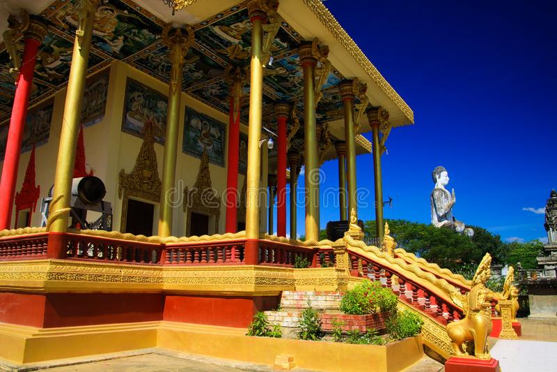 Vista em colunas douradas, em cilindro e na estátua branca de buddha contra o céu azul no templo budista - Wat Ek Phnom, perto de imagens de stock