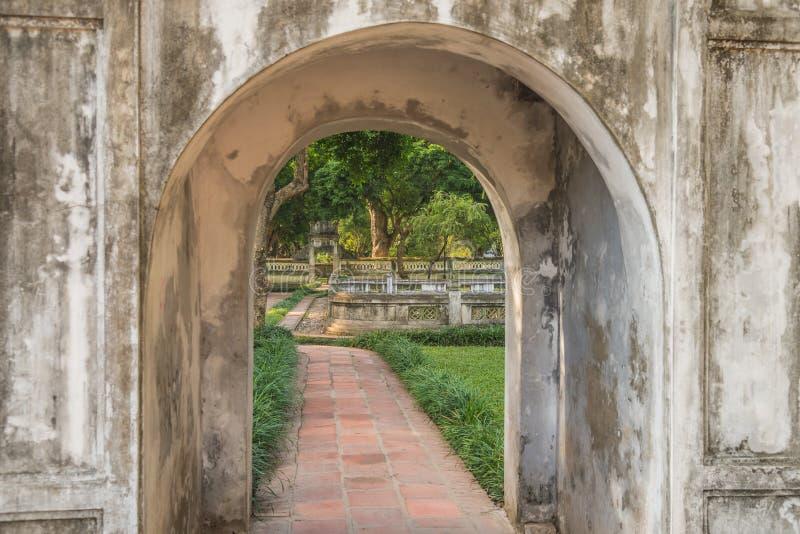 Vista em um jardim formal através de um arco no templo da literatura em Hanoi, Vietname fotos de stock