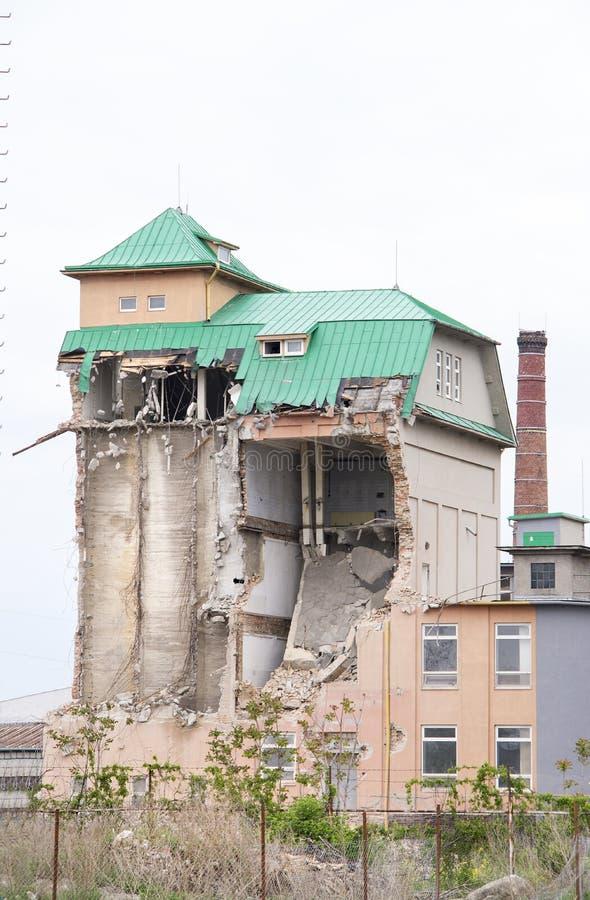 Vista em uma construção industrial parcialmente desmoronada do tijolo com o telhado verde do metal e o céu claro acima Silo indus imagens de stock royalty free