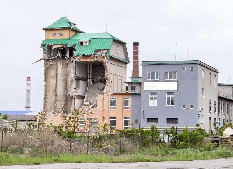 Vista em uma constru??o industrial parcialmente desmoronada do tijolo com o telhado verde do metal e o c?u claro acima Silo indus fotografia de stock royalty free