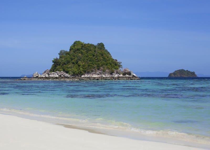 Vista em uma ilha desinibido na lagoa azul da praia branca da areia foto de stock