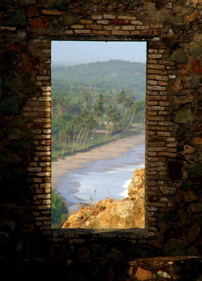 Vista em uma praia ganesa através da janela de um castelo antigo imagem de stock