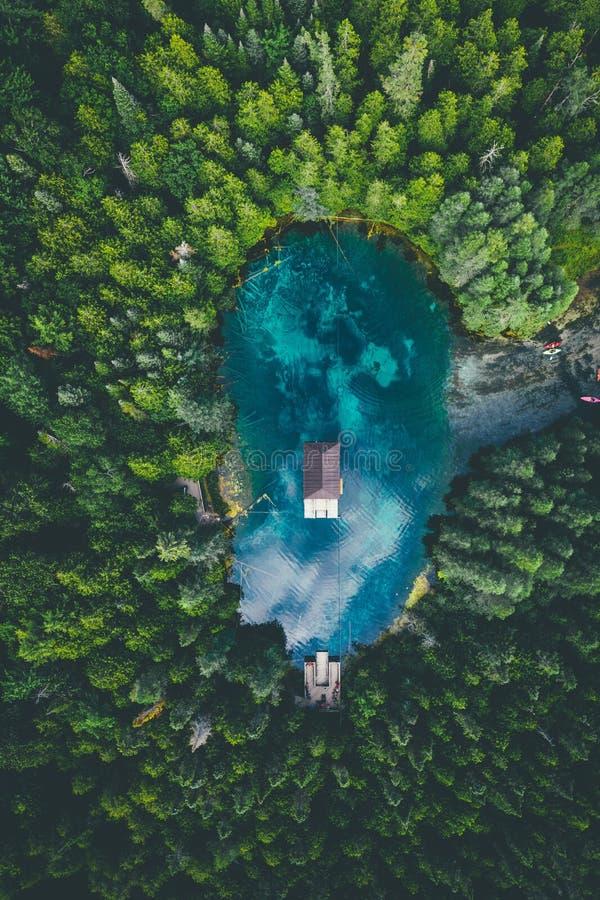 Vista en gran angular de un edificio en un lago rodeado de bosques bajo un cielo nublado foto de archivo