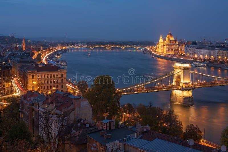Vista escénica de la ciudad de Budapest en la hora azul con el puente de cadena iluminado, el terraplén húngaro del parlamento y  fotos de archivo libres de regalías